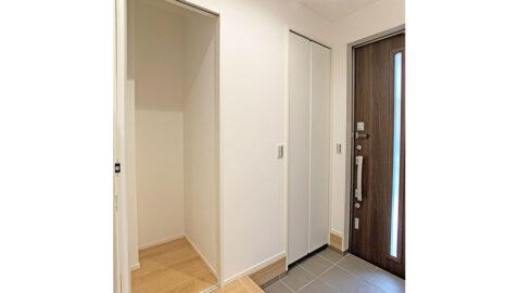 玄関ホールには高さのある収納があり、背の高いワイパーや掃除機などを収納できて便利です。