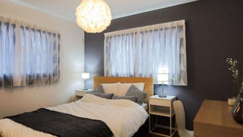 居室(7帖)アクセントクロスに木目のフロアが際立つ清々しい空間。窓位置に配慮し大きな寝具もすっきり納まります。